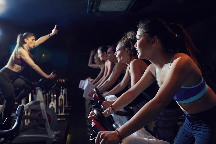 Un grupo de chicas dando una clase de spinning en un gimnasio